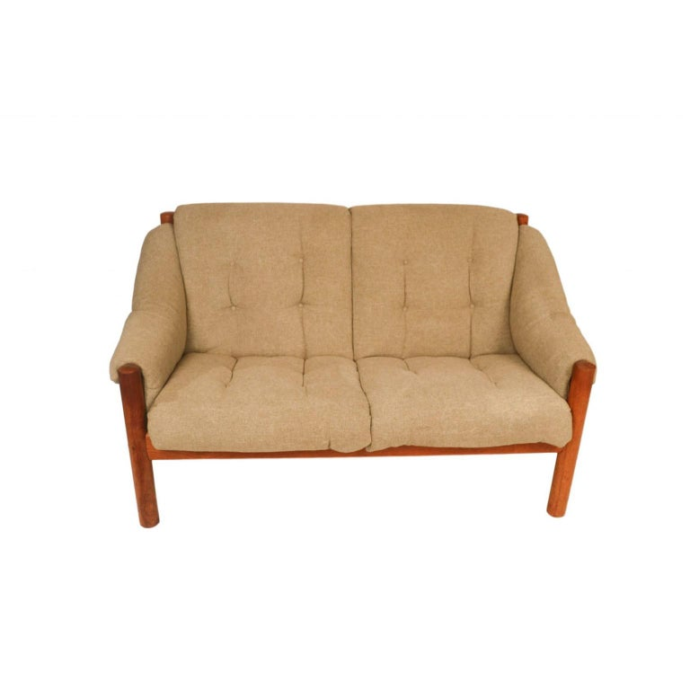A stunning, comfortable, Mid-Century Modern, Danish 2-seat, teak sofa, settee, loveseat, from Domino Møbler, made in Denmark. An exceptional settee both for its form and quality. This loveseat embodies the whimsical fervour of the period, from
