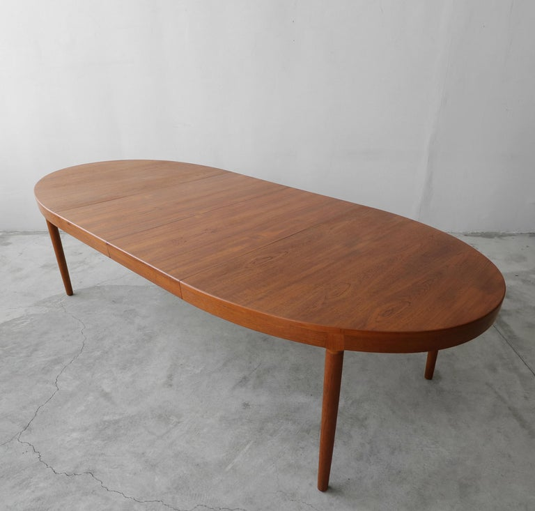 This a beautiful oval shaped Danish teak dining table by Harry Ostergaard for A/S Randers is both Classic in Danish design and very well made, with solid teak details. It has beautiful lines and gorgeous color. This table is a great size closed and
