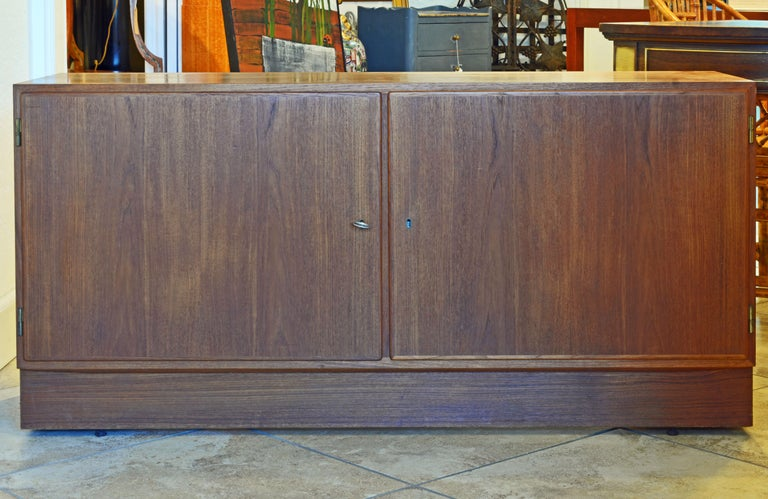 In a Classic Minimalist design this fine piece of furniture shows beautifully grained teak on the top, front and sides. The sideboard features two doors with locks opening up to an interior fitted with drawers and adjustable shelves. The Poul