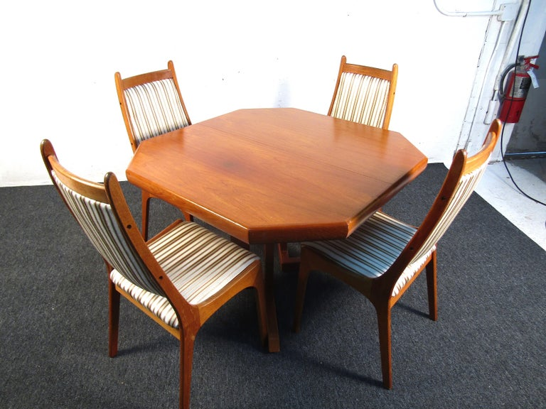 This beautiful teak wood Danish dining set features a beautifully upholstered chair and two additional leaves for when a larger table is needed. Beautiful in design with tons of functionality this set will add a presence to any home. It is able to