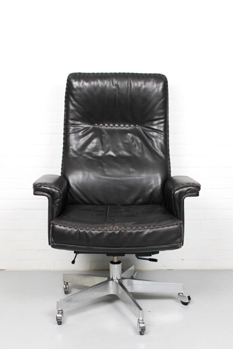 Rare vintage De Sede DS 35 Executive armchair on casters. Hand built to incredibly high standards by De Sede craftsman in Switzerland. This iconic swivel armchair is upholstered in stunning very dark brown aniline leather with superb whipstitch edge