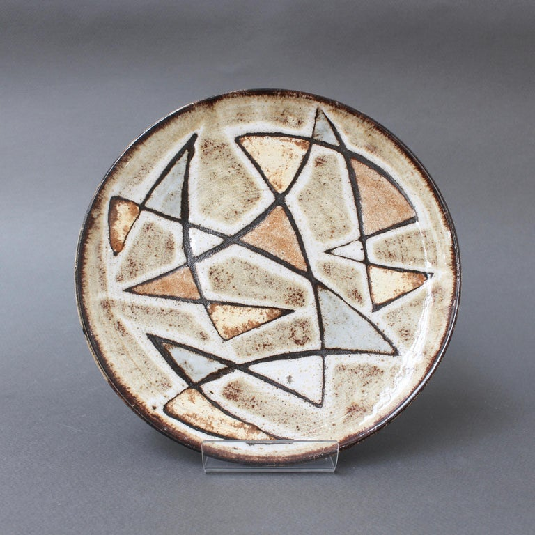 Decorative ceramic plate by Robert Perot, founder of the pottery, Vieux Moulin (circa 1950s), Vallauris, France. Exquisite design with geometric shapes in very muted shades of brown, blue, yellow and green. This is an authentic, collectible