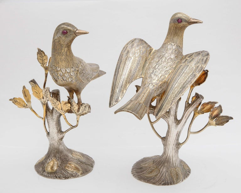 Midcentury decorative pair of sterling silver table birds with real ruby eyes, Mexico, circa 1950s, Tane - maker. Each bird is perched on a tree branch. Both sterling silver figures are parcel-gilt. The measurements are as follows: The bird with its