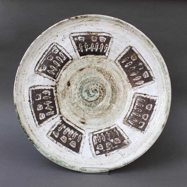 Midcentury decorative plate (circa 1960s) by Albert Thiry (1932-2009). An earthy, glazed centre with swirls of brown and touches of green is encircled, like petals of a flower by deeply engraved rectangles. Inside are leaves and crowns in dark