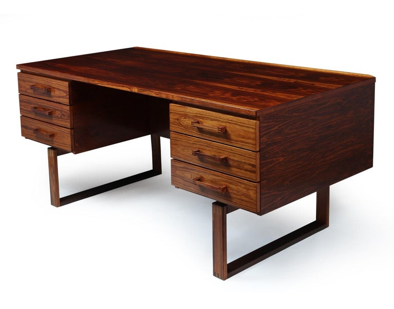 Midcentury desk by Henning Jensen Designed by Henning Jensen and Torbin Valeur in Denmark in the mid-1960s. This rosewood desk has beautiful graining and the exposed finger joint construction. Highlighted by a subtle raised lip along the back edge,