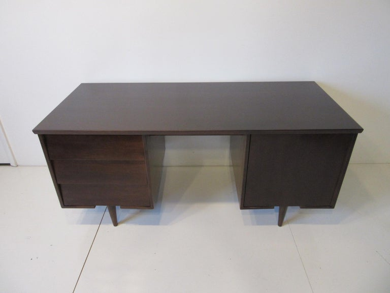 A dark ebony toned wood midcentury desk with three drawers the top one having pen/ pencil divider. The other side has a door and flat file storage with one removable shelve, retains the manufactures ink stamp to the drawer bottom Mengel Bord