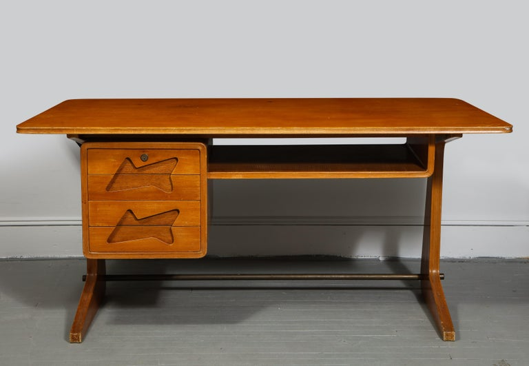 Exquisite mid-century desk in the manner of Gio Ponti, Italy, circa 1950s.   Stunning and inventive design consists of two drawers with fantastic cut-out handles, open shelf, bowed desk top with generous surface space, and handsome angular feet