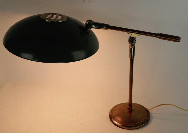Mid-Century Modern adjustable desk lamp designed by Gerald Thurston for Lightolier. The lamp has a saucer disk shade ( 12 in diameter. ) which tilts and pivots, and the support arm ( 22 in L with shade ) will raise and lower, to position and direct