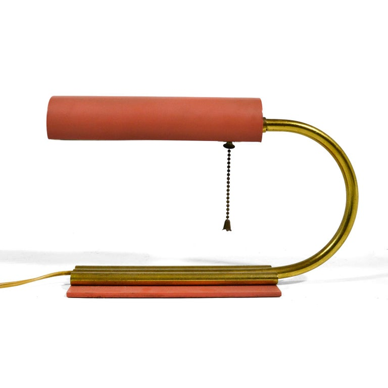 This elegant little desk lamp has an early midcentury or streamline moderne aesthetic. The C-shaped curved brass neck connects the rotating cylindrical head to the base and provides a cord chase. The wonderful salmon pink of the base and head
