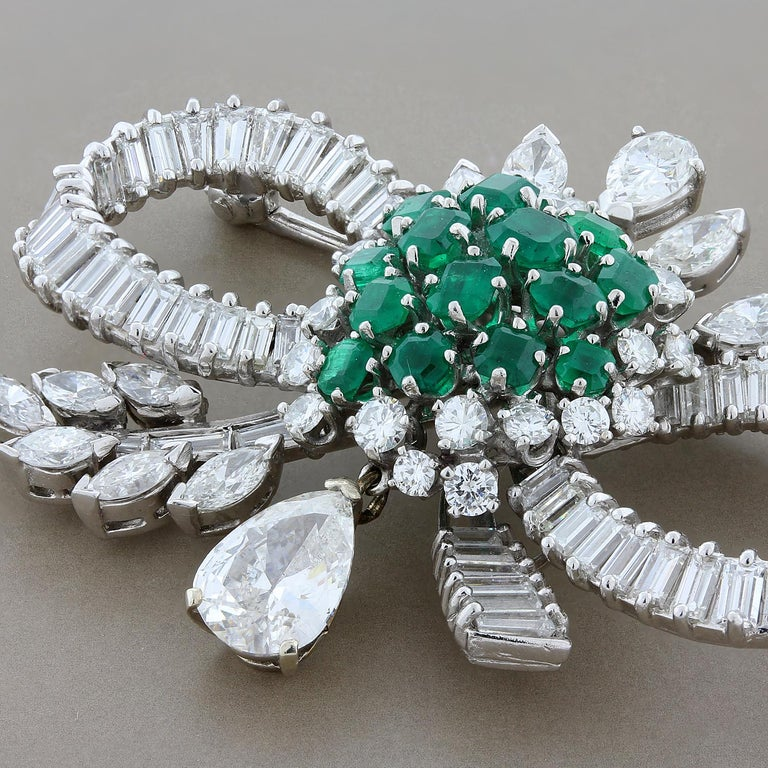 An expertly crafted brooch from the mid 1900's featuring a total of 7 carats of diamonds including a 1.90 carat pear shape diamond drop. In the center of the brooch are 2 carats of fine deep green emeralds giving the piece great color. Set in