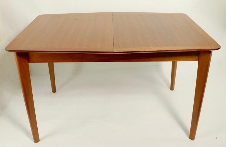 Architectural, sophisticated midcentury dining table by noted English maker Gimson and Slater, retailed by Heals of London. This chic table is asymmetrical having a six sided top which is wider in the center, tapering toward the narrow edges (32.5 -