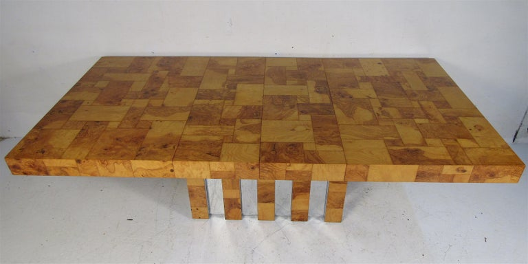 Stunning vintage dining table by Paul Evans for Directional. Beautiful patchwork burl wood design that sits on a pedestal base with chrome trim. This dining table includes two leaves allowing it to extend from 60.5-90 inches wide. A unique design