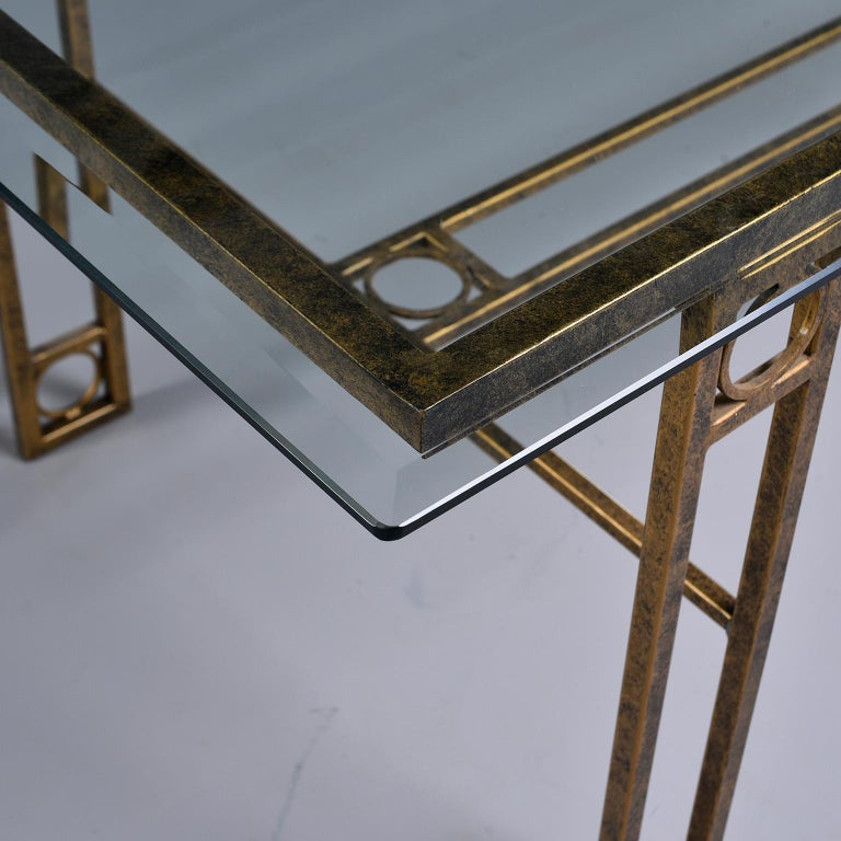 Dining table has an iron base with a burnished gold finish and open work design of rectangles and circles. Rectangular glass top has beveled edge and is in very good vintage condition. Unknown maker. Found in England, circa 1970s.
