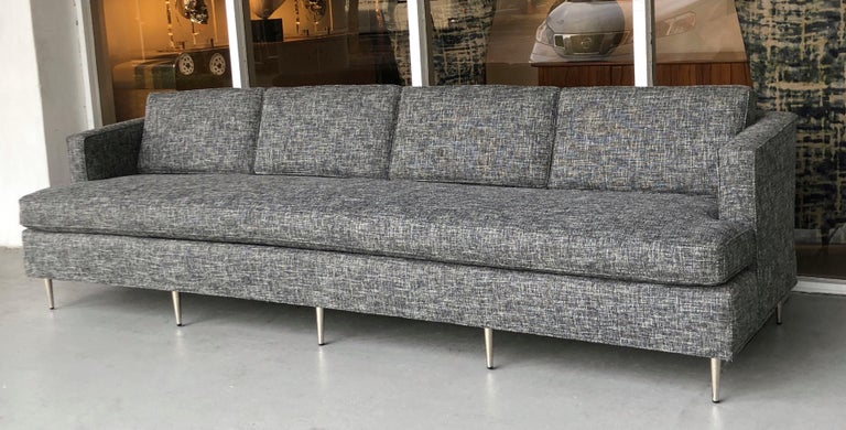 A midcentury sofa in the style of Dunbar. Newly upholstered in charcoal and white bluocle. New stainless legs.