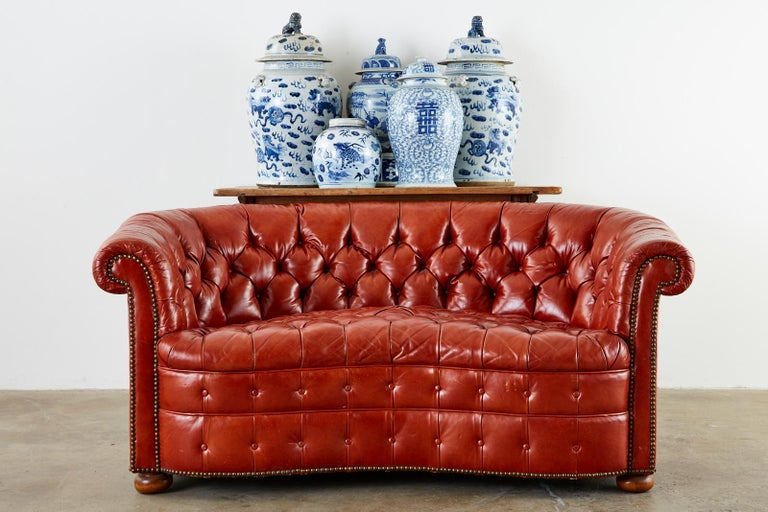 Stylish Mid-Century Modern English Chesterfield settee or loveseat featuring a curved, round back and a serpentine front seat. The kidney style shape has a hardwood frame covered with orange tufted leather hides bordered with brass tack nailheads.