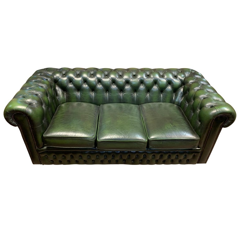 A quintessentially English mid-20th century emerald tufted chesterfield sofa with a rich dark emerald green leather upholstery with three cushions, rolled and tufted arms and back, and a tufted front panel, all with brass nailhead trim. The sofa