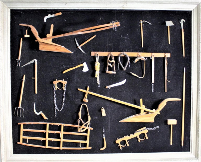 This framed collection of over two dozen handcrafted miniature antique farm implements are all unsigned, but presumed to have been made in Canada in circa 1969 in a Folk Art style. The implements are hand carved and handcrafted of wood and leather