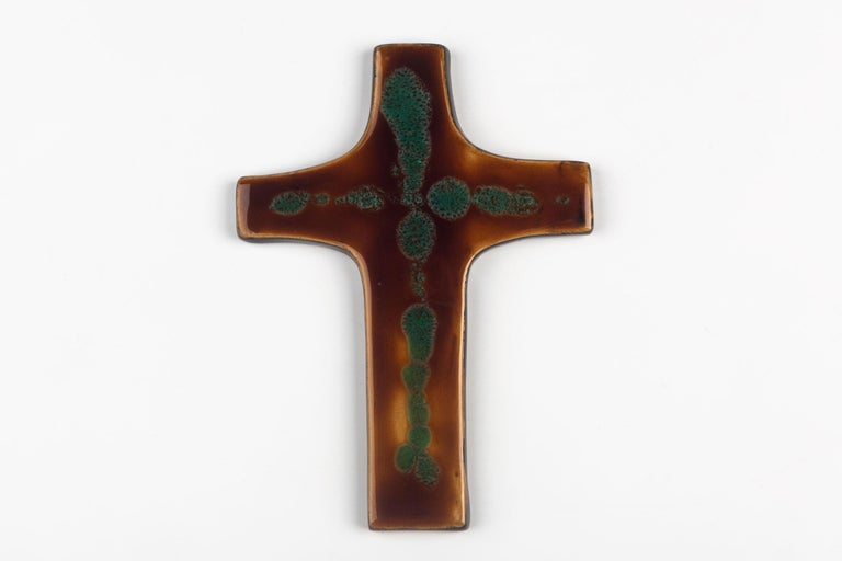 Mid-century European ceramic wall cross in brown and green, with slight texture to the glazed ceramic and a mastery of depth of color. From a large collection of crosses handmade by Flemish artisans.  From modernism to brutalism, the crosses in our