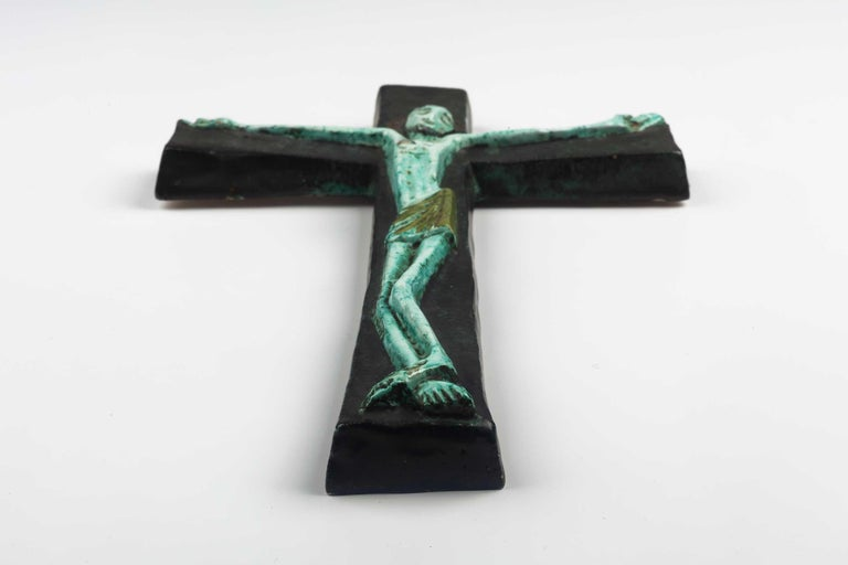 Midcentury European wall cross in blue, green tones with angelic Christ figure in volume. From a large collection of vintage crosses handmade by Flemish artisans.   From modernism to brutalism, the crosses in our collection range from being as