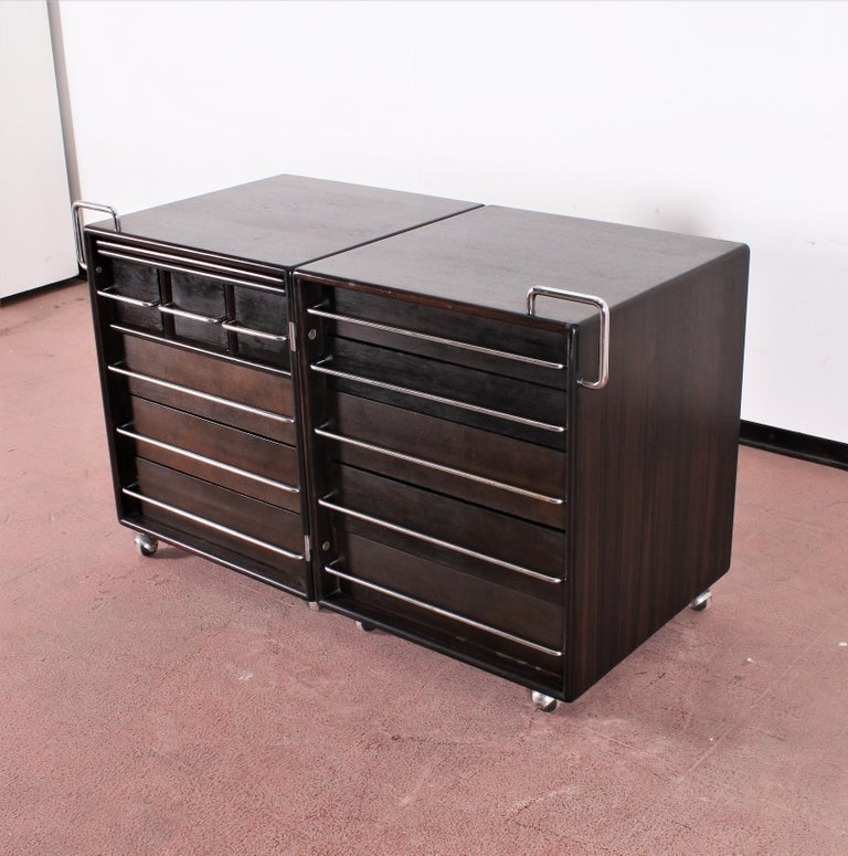 Beautiful chest of drawers with dressing table, with two compartments on wheels, connected  by hinges, opening with a compass.  Realization in  dark solid wood with chromed steel handles . Designed by Fabio Lenci, produced by Bernini in the