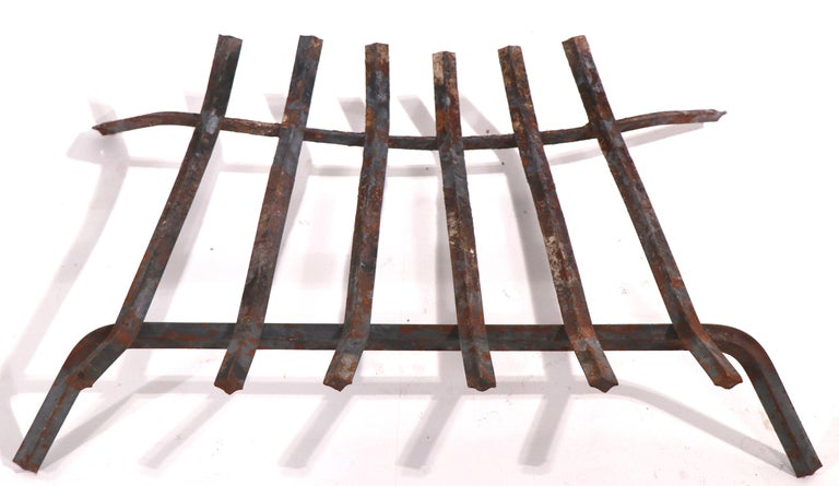 Iron log holder, fireplace insert grate. Nice vintage example, shows expected wear to finish, normal and consistent with age and use.   W - 24 H at Front - 6 H at Back - 4 D - 16 inches.