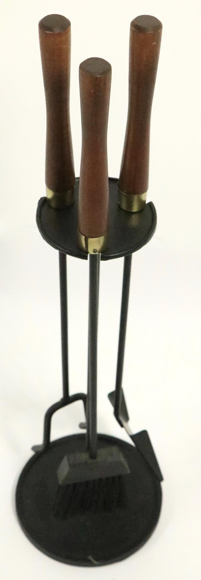 Classic midcentury fireplace tool set by Seymour Manufacturing Company. Three tools, shovel, brush and poker, and the stand . The brass collars which cap the wood handles have splits, please see images.