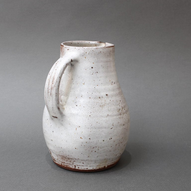 Mid-Century French ceramic pitcher by Jeanne & Norbert Pierlot (circa 1960s). With an off-white base and brown sandstone accents, this small, rustic pitcher with handle and spout is a delight. The glazed parts that are predominantly off-white are