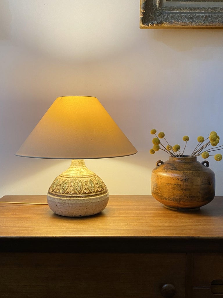 Midcentury ceramic glazed table lamp (circa 1960s) by Marcel Giraud, Vallauris, France. A piece with a graceful, rounded shape with wide centre in a muted chalk-colored base. This stunning lamp has a palm tree and leaf motif just above the centre