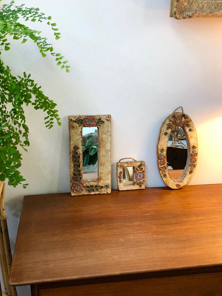 Ceramic flower-motif wall mirror with glazed leaves attributed to La Roue, Vallauris, France, circa 1960s. A charming, decorative small mirror with rustic but colorful details surrounding the narrow, rectangular mirror. In good vintage condition