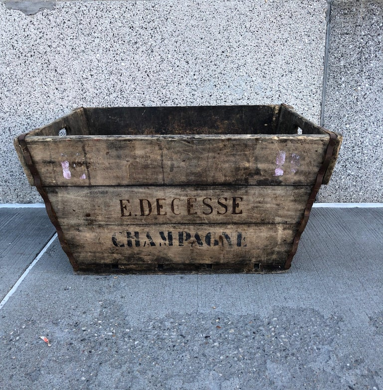 A stunning, beautifully worn wooden vintage champagne harvest basket with stenciled name of vineyard prominently featured on both sides. This sturdy, large wooden box is a natural for firewood, or as an entry way piece to hold shoes, toys, or