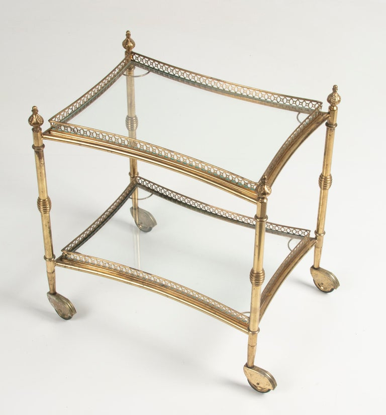 A copper mid century bar cart. The trolley has two levels of glass. The trolley have a copper cut-out raised edge. The copper swivel wheels have a little wear on the copper. It's made in France, around 1960-1970. The cart can be disassembled and can