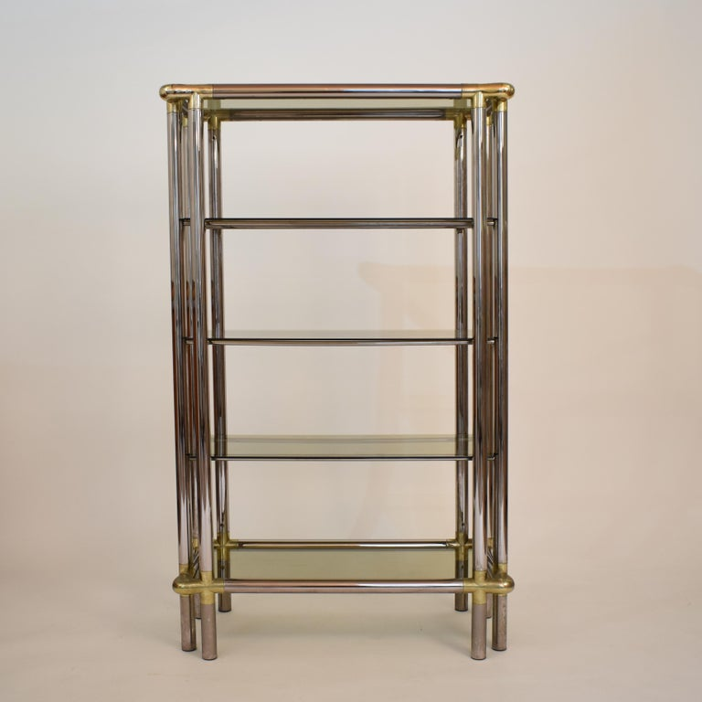 This beautiful Mid-Century Hollywood Regency display glass shelf was made in France in the 1970s. It is made in high quality. The étagère with the chrome tubes and brass corners are fitting elegant together. A wonderful piece of furniture for a