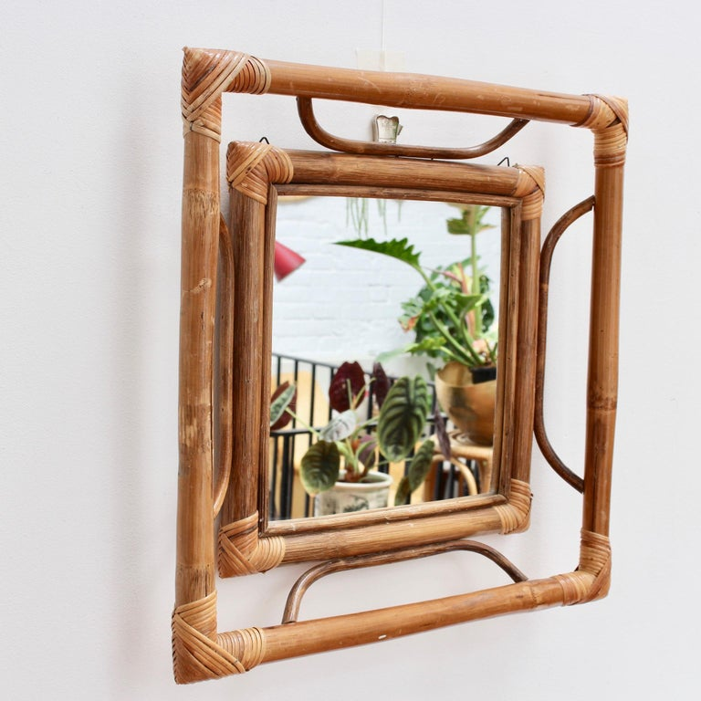Midcentury French Indochine-style bamboo and rattan wall mirror (circa 1960s). A very unusual and rare find with a framed square mirror within a larger square bamboo frame - a frame within a frame. The minimalist styling features bamboo and rattan