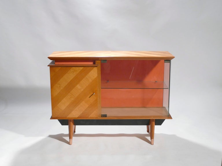 Warm light brown oak and rich copper form a beautiful color palette in this cabinet vaisselier from the 1950s. On the front and top of the cabinet, the oak displays a striped lightwood/dark wood pattern that feels fun and very much of the era, while
