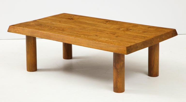 This coffee table was designed in the 1950s and 1960s in France under the inspiration of Charlotte Perriand or Pierre Chapo. Crafted in solid oak, it is composed of four cylindrical feet and a thick rectangular top, assembly by tongues and grooves