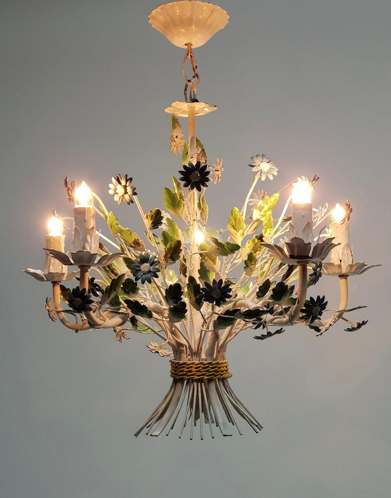 This elegant, midcentury chandelier was crafted in France, circa 1960. The charming hanging light fixture has five lights and is embellished with realistic blue flowers and green leaves. The round chandelier is in good vintage condition and has its