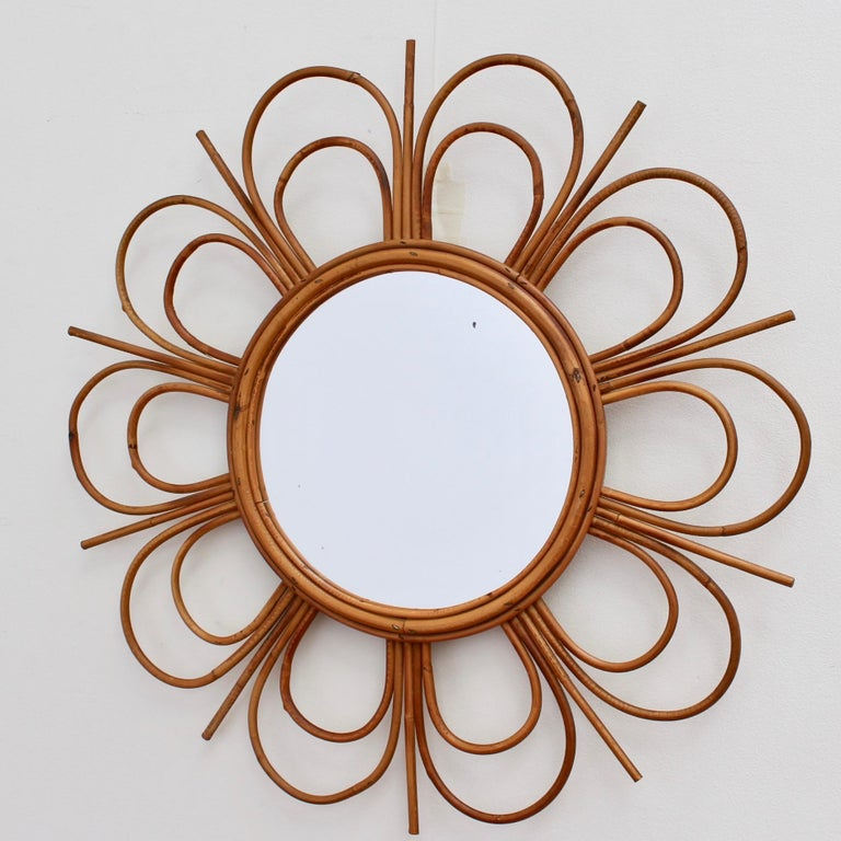 Midcentury French rattan flower-shaped wall mirror, circa 1960s. Very unique, charming, uplifting, stylish and collectible, this mirror is in overall good vintage condition commensurate with its age and usage. There are some evident blemishes on the