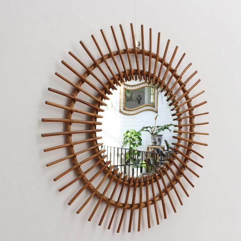 Large midcentury French rattan sunburst mirror (circa 1960s). A vintage collectible classic with sunburst halo and spokes in rattan cane. A designer's favorite, this mirror is in good condition consistent with age and use showing a characterful