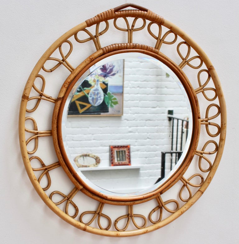 Midcentury French rattan round wall mirror (circa 1960s). This vintage mirror is formed by two concentric circles framing the glass. They are connected by sixteen rattan flower motif designs creating a chic and appealing piece. This is a very rare