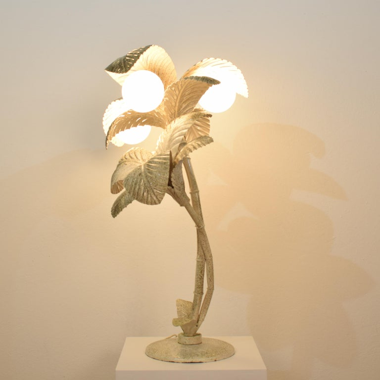 This beautiful midcentury French palm lamp was made circa 1970. It is made out of metal which is lacquered in white and has some golden sparkle on top. It is in a beautiful original condition. The 3-light bulbs are matted opaline glass which got