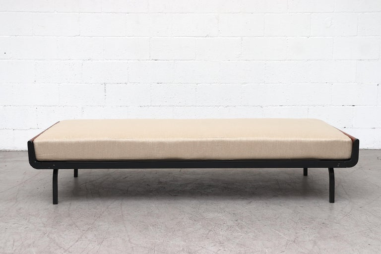 Mid-Century sled style daybed with teak ends and grey enameled square metal legs for Auping. Newly upholstered tan mattress on wire mesh support with original manufacturer stamp. In original condition with some enamel loss and wear consistent with