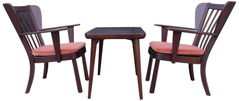 This wonderful set of Canada chairs and side table represents early transitional pieces to Scandinavian Modern. Designed in 1939 for Fritz Hansen, this set is comprised of two armchairs and a table, made of solid stained beech. Petite wingback easy