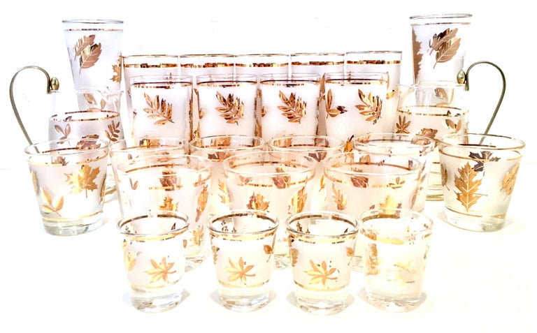 Mid-Century Modern frosted & 22-karat gold leaf motif drinks set of 26 pieces. Set includes, nine cocktail glasses, five Tom Collins glasses, four high ball glasses, four shot glasses, two pilsner glasses and two brass handle