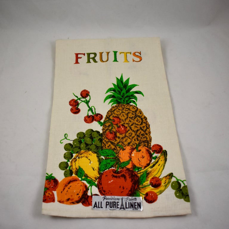 A set of two linen towels from the midcentury era, still brightly colored, with the original labels, never used. Printed in a style typical of the era, with a type face in mixed colors. Hemmed on all sides.  One towel is titled Fruit, showing a