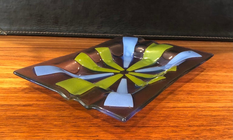 """Midcentury fused art glass ashtray by Higgins, circa 1950s. The pattern, called """"Tortoiseshell"""" is created by sandwiching enameled glass panels of periwinkle blue and avocado green between tinted lavender glass panels to create an atomic starburst"""