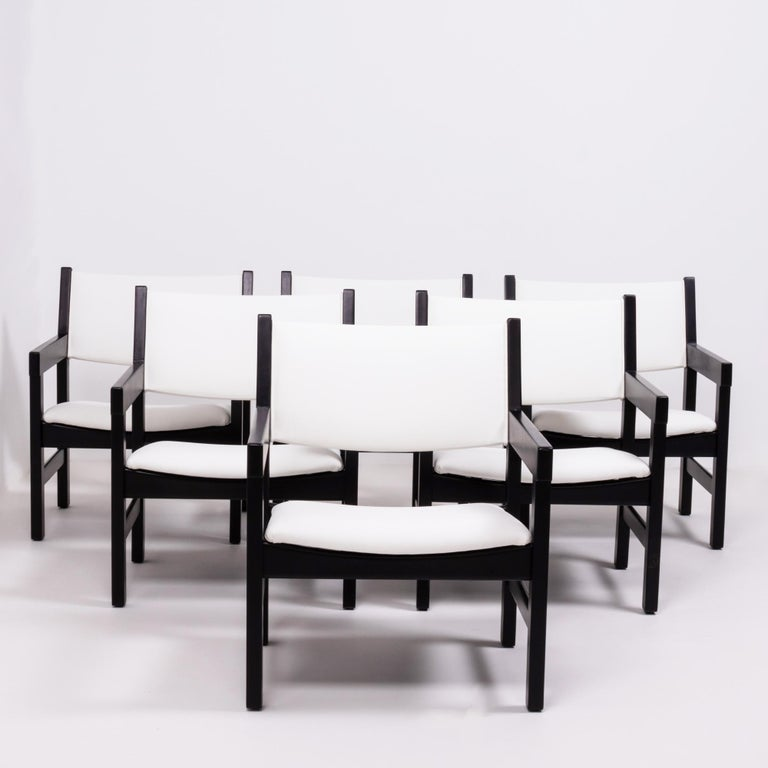 Designed by Hans J. Wegner for GETAMA, this set of six GE 151 chairs are a Classic example of Mid-Century Modern design.  Featuring angular black painted beechwood frames and arms, the newly restored chairs have padded seats and backrests which