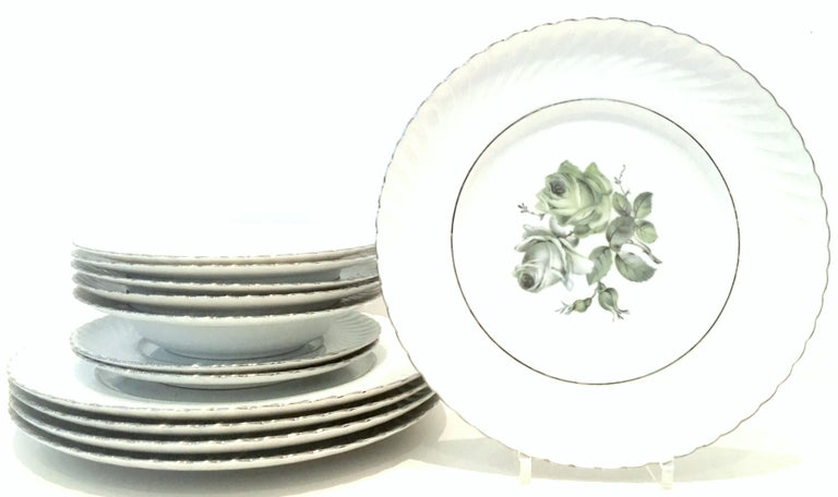 Mid-20th century German porcelain and platinum dinnerware set of twelve pieces by, Royal Tettau.. This German porcelain pattern by Royal Tettau features a bright white ground, swirled edge with a blue and green central rose motif and silver platinum