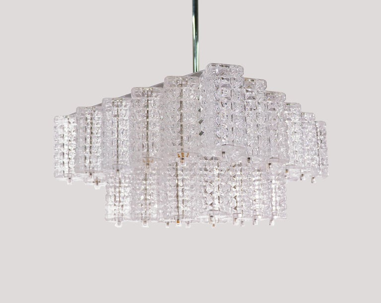 Elegant chandelier with faceted rectangular glass elements on a nickel plated frame with a chromed rod and canopy. Manufactured by Austrolux, Vienna, Austria in the 1960s.   Measures: w 16