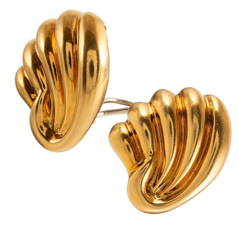 Swirling strokes of 18 karat yellow gold are fashioned into a wing-like or shell design. The earrings are simply charming, with equal parts sophistication and whimsy. They measure approximately 1 inch square and are currently clips, however a post