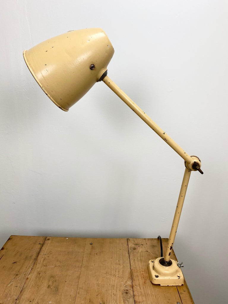 This beige industrial-style iron table lamp is made in former Czechoslovakia. It has an adjustable shade, three adjustable joints, a new porcelain socket for E 27 light bulbs and new wire. The switch is situated directly on the shade. Fully